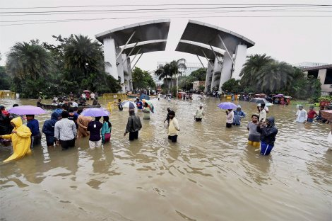 Chennai: People wade through waterlogged road following heavy rains at Porur in Chennai on Wednesday. PTI Photo (PTI12_3_2015_000031B)